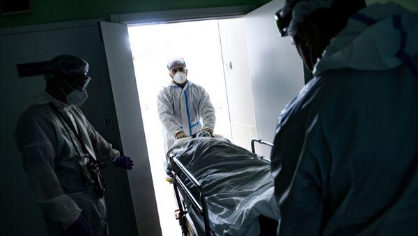 Медицинские работники оказывают помощь пациенту с COVID-19