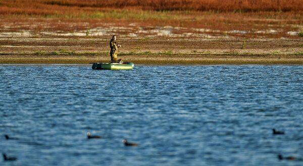 Мужчина ловит рыбу на Бахчисарайском водохранилище в Крыму