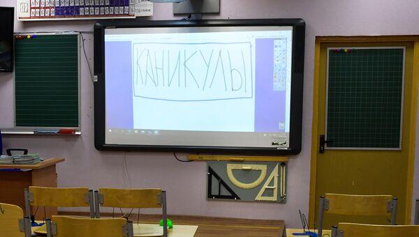 Надпись Каникулы на мониторе в учебном классе в московской школе No 2127