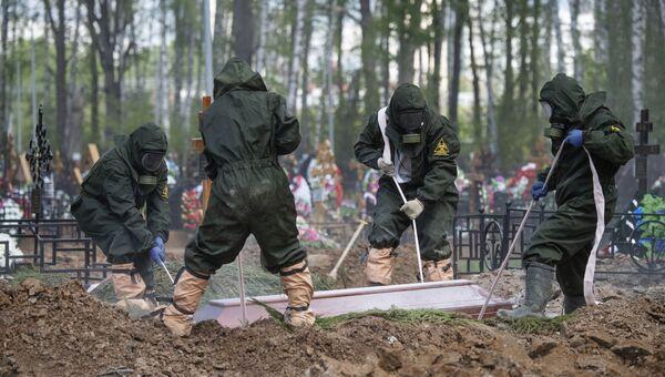 Сотрудники Бутовского кладбища в Москве опускают гроб с телом умершего от коронавируса в могилу