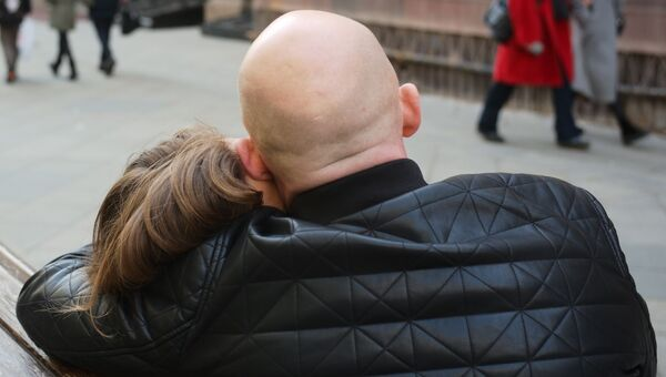 Пара обнимается на скамейке