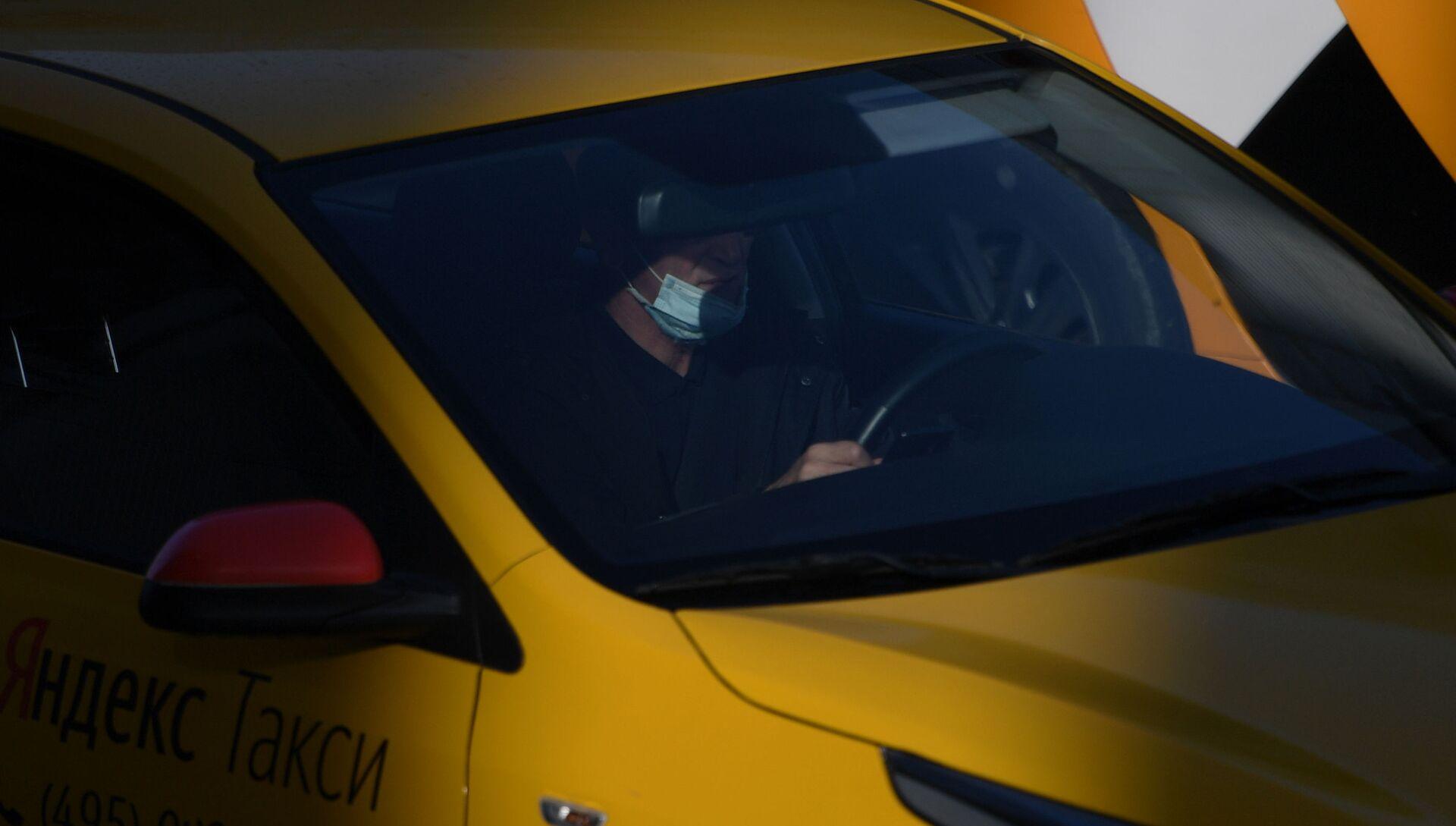 Водитель в защитной маске за рулем такси на одной из улиц - РИА Новости, 1920, 05.08.2021