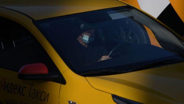 Водитель в защитной маске за рулем такси на одной из улиц
