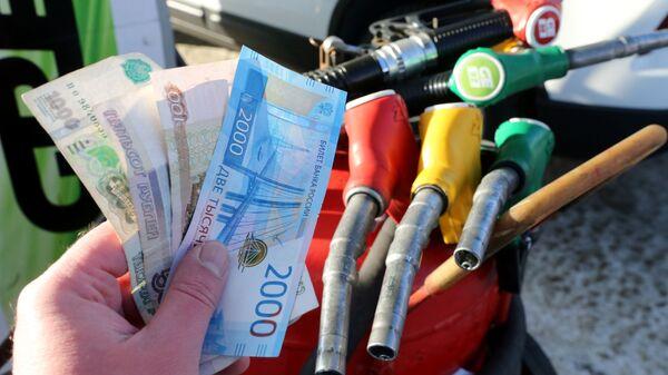 Деньги на оплату топлива на АЗС. Архивное фото