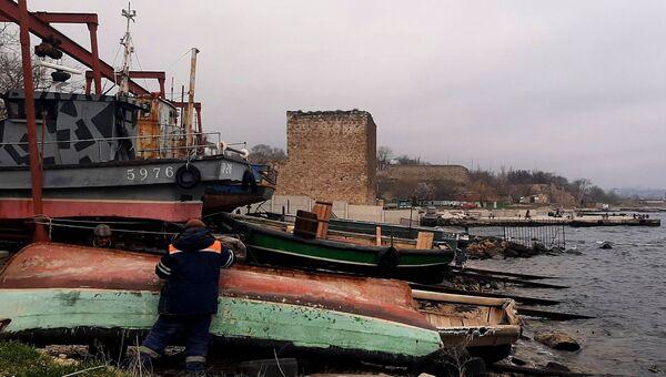 Рыбацкие лодки-фелюги на фоне Доковой башни XIV века и бетонного пирса. Феодосия
