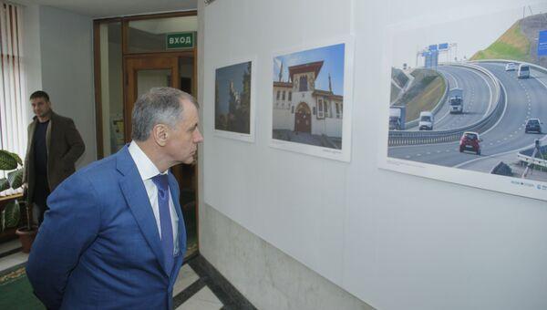 Владимир Константинов рассматривает выставку РИА Новости Крым к семилетию Крымской весны