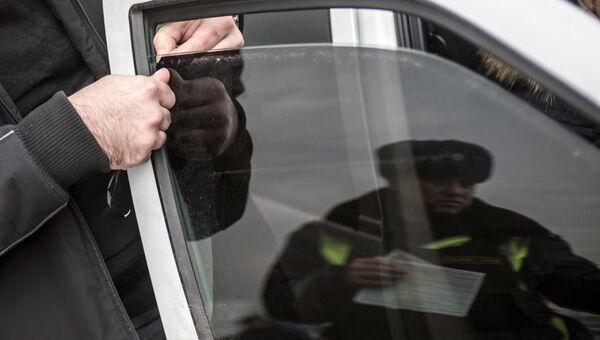 Автовладелец снимает тонировочную пленку со стекла своего автомобиля