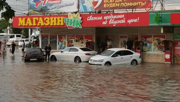 Легковые автомобили спасаются от потопа на тротуаре