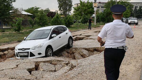 Обрушившийся участок дороги после урагана и аномального ливня на проспекте Суворова в Симферополе