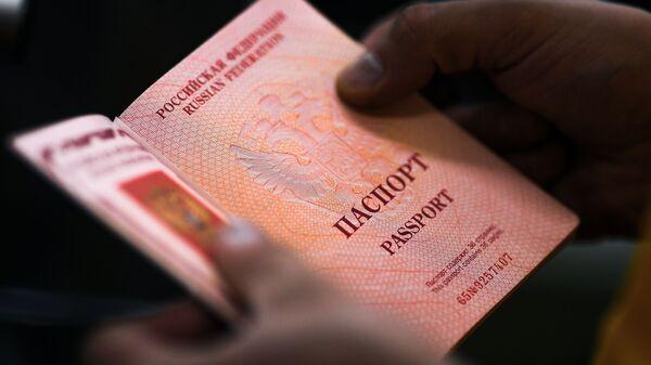 Сотрудник с паспортом РФ в руках на фабрике АО Гознак в Москве