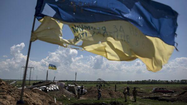 Украинский флаг развевается на украинской позиции в Марьинке, недалеко от Донецка, восточная Украина, пятница, 5 июня 2015 года. Архивное фото