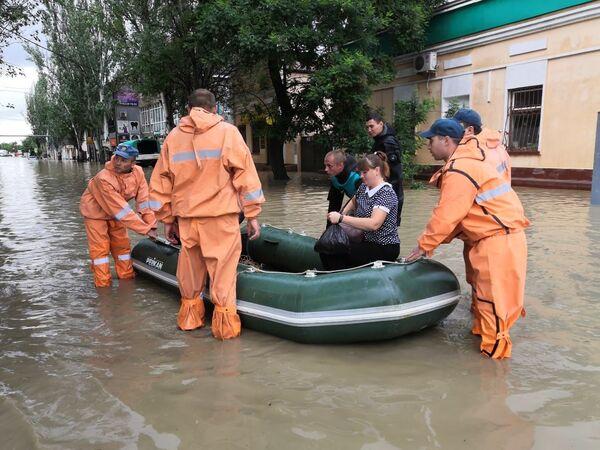 Спасатели эвакуируют людей на лодке во время подтопления в Керчи
