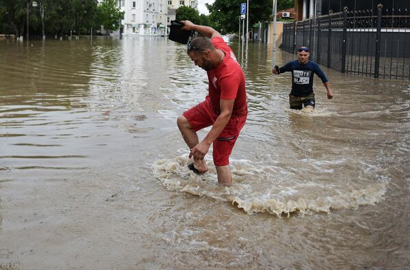 Мужчины на одной из улиц Керчи после сильных ливней