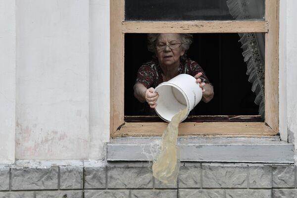Жительница Керчи вычерпывает воду из дома ведром