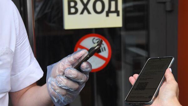 Посетитель показывает специальный QR-код на экране смартфона на входе в кафе