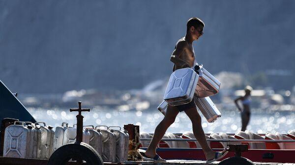 Мужчина несет канистры для топлива на причале в Судаке