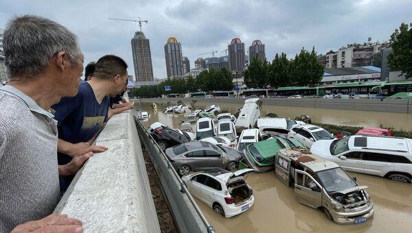 21 июля 2021 года. Люди смотрят на машины, утонувшие в паводковых водах после проливных дождей в городе Чжэнчжоу в центральной провинции Хэнань Китая