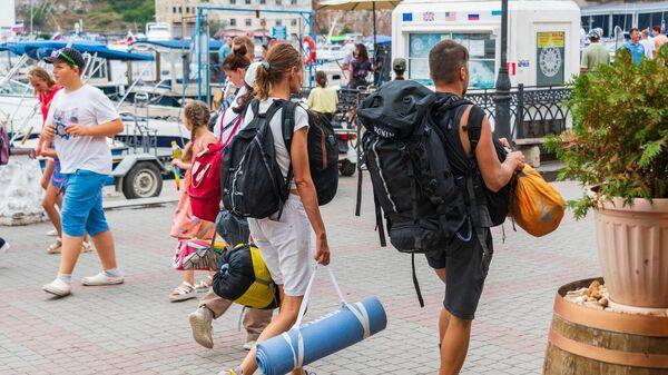 Туристы с рюкзаками на набережной Балаклавы