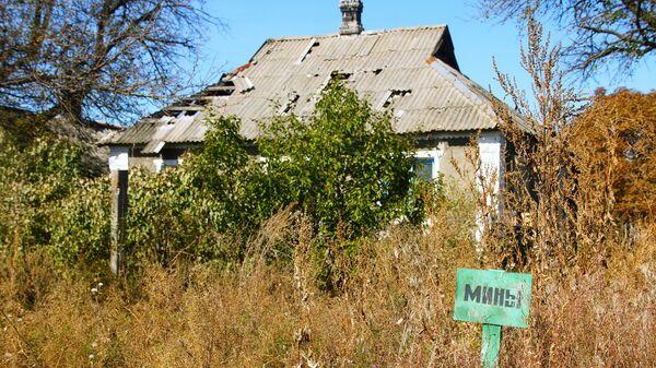 Табличка с надписью Мины возле разрушенного дома в Луганской области
