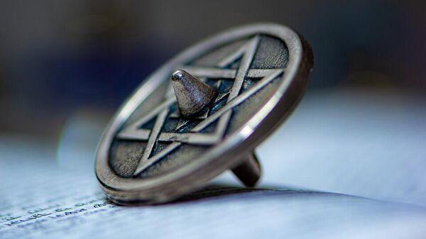 Дрейдл — четырёхгранный волчок. На каждой грани дрейдла написана еврейская буква: нун, гимель, хей и шин. Это начальные буквы слов в предложении נס גדול היה שם (Нес гадоль хайя шам — Чудо великое было там)