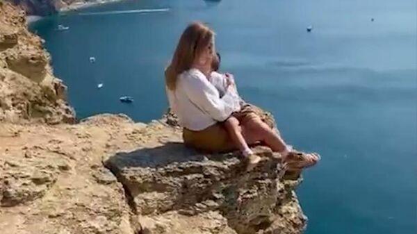 Женщина с ребенком позирует на обрыве скалы. Скриншот видео из соцсетей
