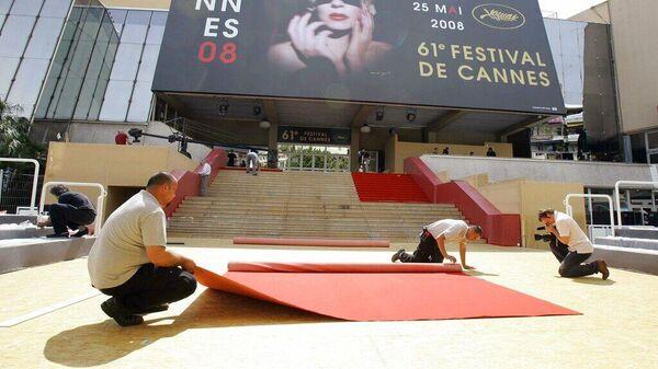 Рабочие раскатывают кусок красной ковровой дорожки, которую они собираются закрепить на ступенях дворца Каннского кинофестиваля накануне открытия. 13 мая 2008 года
