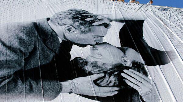 Рабочие установили гигантский официальный плакат 66-го Каннского кинофестиваля. На плакате изображены поцелуй Пола Ньюмана и Джоанн Вудворд на съемочной площадке фильма Новый вид любви (1963 год). 13 мая 2013 года