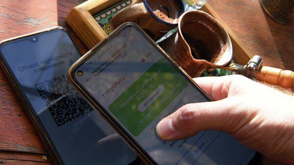 QR-код на экране смартфона в кафе. Архивное фото