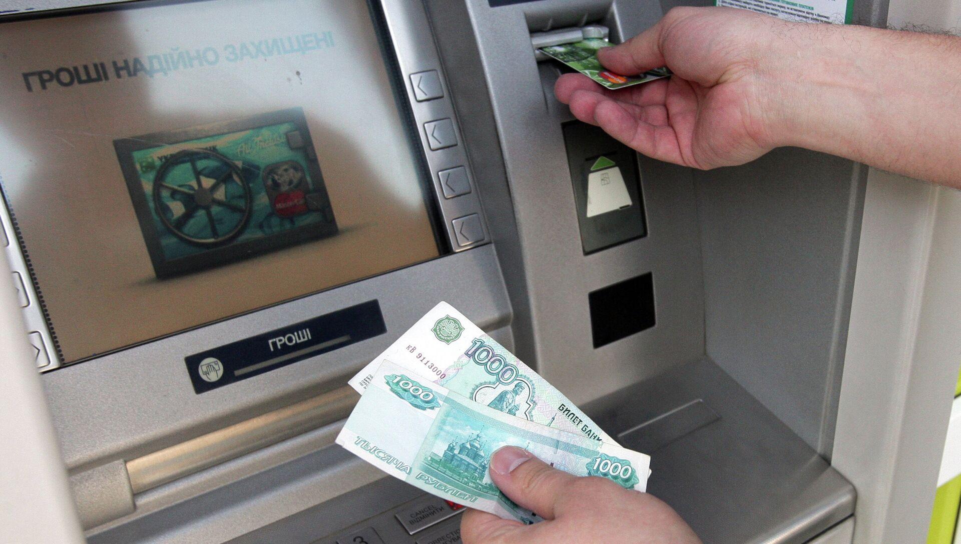 Житель Симферополя снимает наличные деньги через банкомат. Архивное фото - РИА Новости, 1920, 15.09.2015