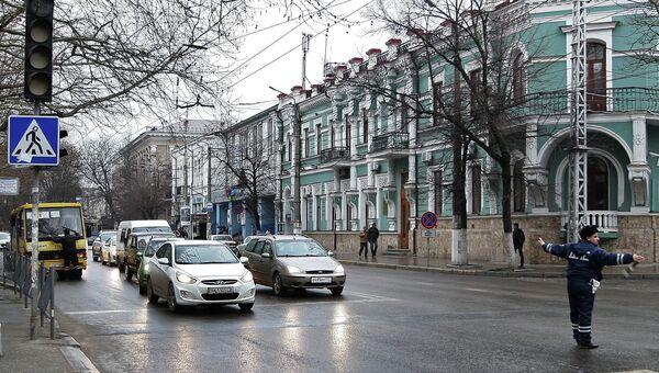 Сотрудник дорожно-постовой службы регулирует движение на одной из улиц Симферополя