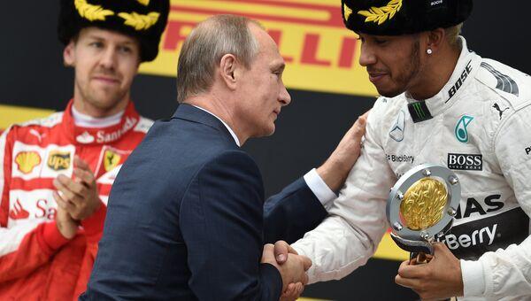 Президент России Владимир Путин (в центре) вручает Кубок Гран-при России гонщику команды Мерседес Льюису Хэмилтону (справа)
