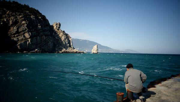 Мужчина ловит рыбу в Крыму.