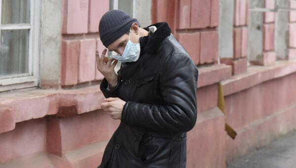 Молодой человек в защитной маске на улице Симферополя