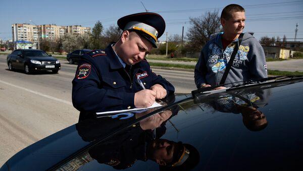 Сотрудник мобильного поста ДПС ГИБДД оформляет предупреждение о необходимости замены украинских номеров в течение 10 дней
