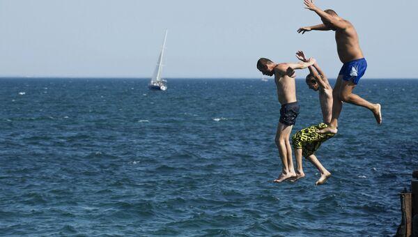 Мужчины прыгают в Черное море в городе Евпатории