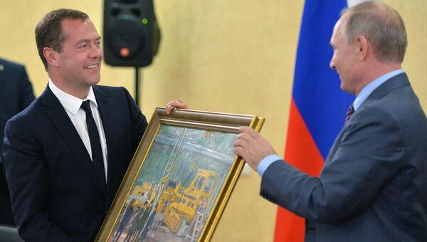 Президент РФ Владимир Путин дарит председателю правительства РФ Дмитрию Медведеву на его день рождения картину В цеху