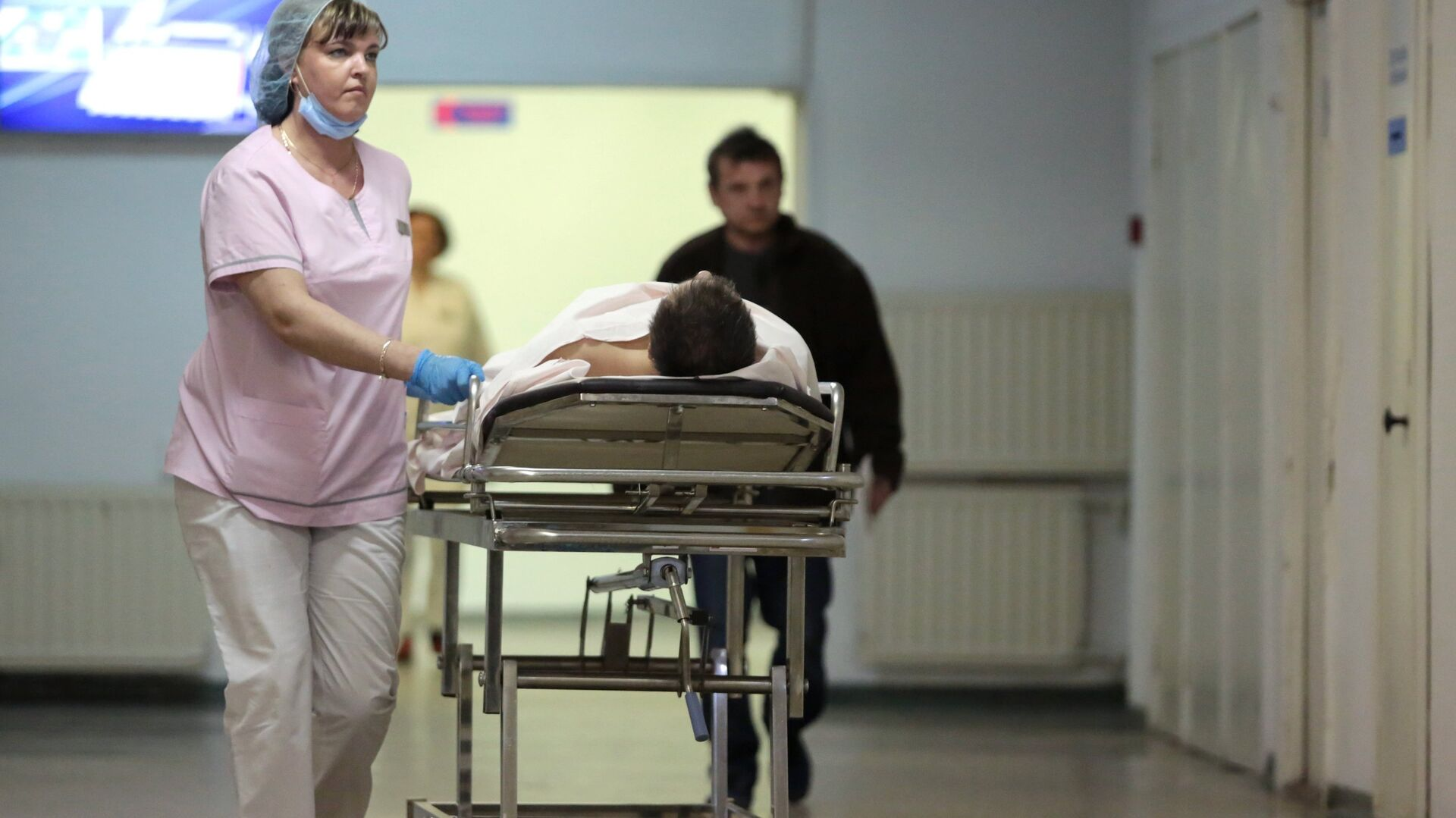 Сотрудница транспортируют пациента в НИИ скорой помощи имени И.И. Джанелидзе в Санкт-Петербурге - РИА Новости, 1920, 12.10.2021