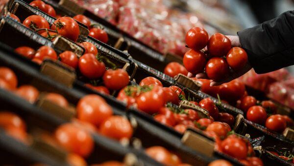 Посетитель выбирает помидоры в супермаркете