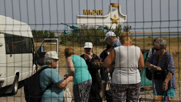 Люди в буферной зоне пункта пропуска Джанкой на границе России и Украины