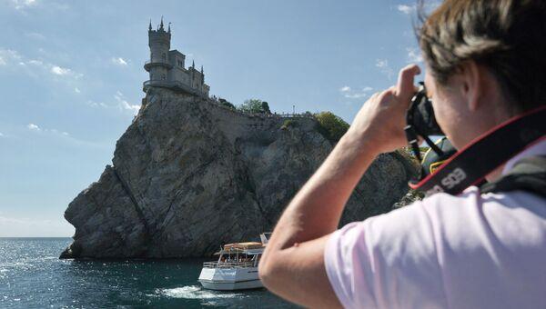 Турист фотографирует замок Ласточкино гнездо