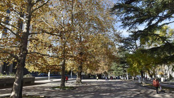 Прохожие в сквере возле здания Государственного совета Республики Крым. Осень в Симферополе