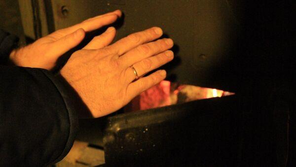 Мужчина греет руки в пункте обогрева, организованного МЧС
