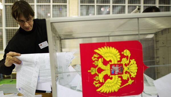 Члены участковой избирательной комиссии высыпают бюллетени для подсчета голосов на одном из избирательных участков в Новосибирске. 18 марта 2018