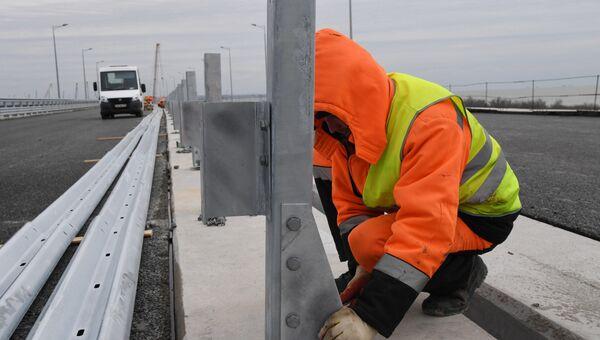 Установка ограждения на готовом участке дороги, ведущей к Крымскому мосту на острове Тузла