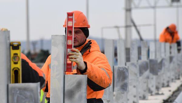 Установка ограждения на готовом участке дороги, ведущей к Крымского мосту на острове Тузла