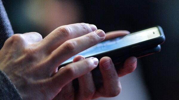 Смартфон в руках мужчины. Архивное фото