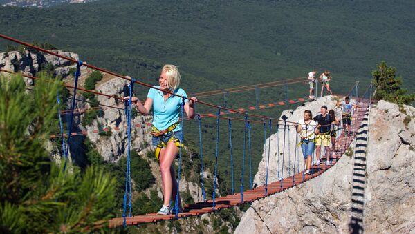 Туристы идут по веревочной лестнице между зубцами горы Ай-Петри в Крыму