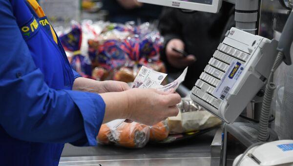 Кассир считает деньги в супермаркете. Архивное фото