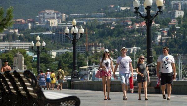 Отдыхающие гуляют на центральной набережной Ялты