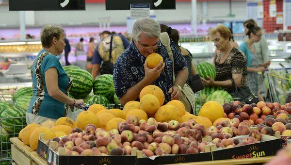 Покупатели в отделе фруктов одного из гипермаркетов